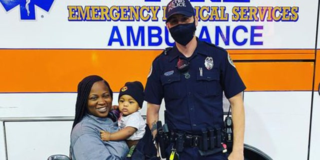 Metro Nashville Police Officer Philip Claibourne poses for a photo with Tanisha Rutledge, 29, and her 9-month-old baby boy.
