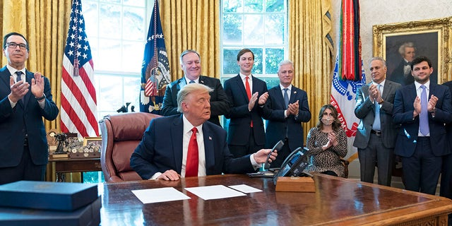 President Trump hangs up a phone call with the leaders of Sudan and Israel, as Treasury Secretary Steven Mnuchin, left, Secretary of State Mike Pompeo, White House senior adviser Jared Kushner, National Security Adviser Robert O'Brien, and others applaud in the Oval Office of the White House, Friday, Oct. 23, 2020, in Washington. (AP Photo/Alex Brandon)