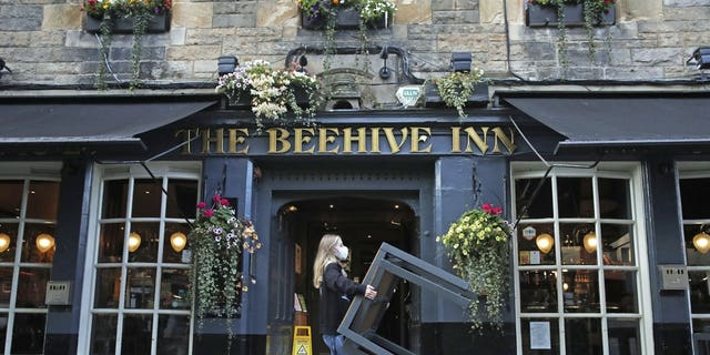 A worker removes tables from outside the Beehive Inn, as temporary restrictions announced by First Minister Nicola Sturgeon to help curb the spread of coronavirus have come into effect at 6 p.m. Friday in Edinburgh. (Andrew Milligan/PA via AP)