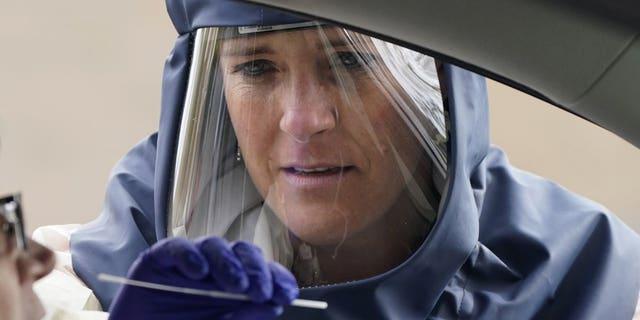 Salt Lake County Health Department public health nurse Lee Cherie Booth performs a coronavirus test on Friday in Salt Lake City. (AP Photo/Rick Bowmer,