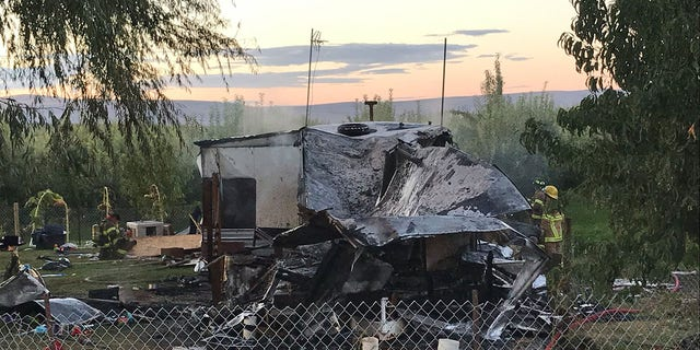 Firefighters examine the charred remnants of the trailer home after it was engulfed in flames early Sunday.