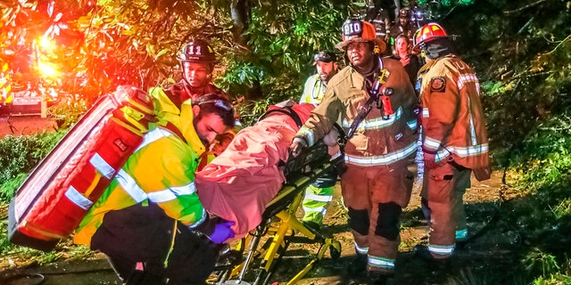 Atlanta firefighters transport a man they freed who was trapped in his third-floor bedroom after a tree came crashing down on a home on Brookview Drive in Atlanta, as Tropical Storm Zeta sped across the Southeast Thursday, Okt.. 29, 2020.