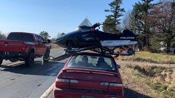 Wisconsin trooper stops driver hauling snowmobile atop sedan