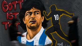 Spanish soccer player sits during Diego Maradona tribute before match