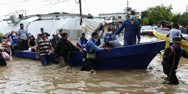 Police help residents move to higher ground after they were rescued from a flooded area, in Planeta, Honduras, Nov. 6. As the remnants of Hurricane Eta moved back over Caribbean waters, governments in Central America worked to tally the displaced and dead, and recover bodies from landslides and flooding that claimed dozens of lives from Guatemala to Panama. (AP Photo/Delmer Martinez)