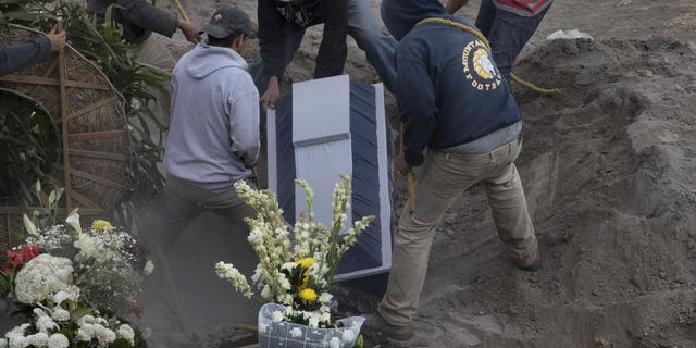 Workers place the coffin of 86-year-old Gabina Salgado Husca, who died of complications related to the new coronavirus, into her grave in the Valle de Chalco municipal cemetery on the outskirts of Mexico City, Wednesday, Nov. 18, 2020. (AP Photo/Marco Ugarte)