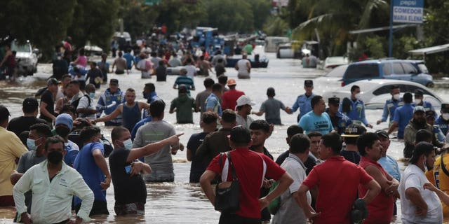 Residents wade through a flooded road in the aftermath of Hurricane Eta in Planeta, Honduras, Nov. 5. The storm that hit Nicaragua as a Category 4 hurricane on Tuesday had become more of a vast tropical rainstorm, but it was advancing so slowly and dumping so much rain that much of Central America remained on high alert. (AP Photo/Delmer Martinez)