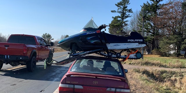 This undated photo provided by The Wisconsin Department of Transportation shows a snowmobile strapped to the roof of a Toyota Corolla in northwest Wisconsin Sunday Nov. 1, 2020.