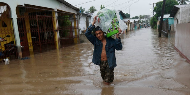 A man walks in knee-deep floodwaters carrying belongings in San Manuel, Honduras, Wednesday, Nov. 4, 2020.