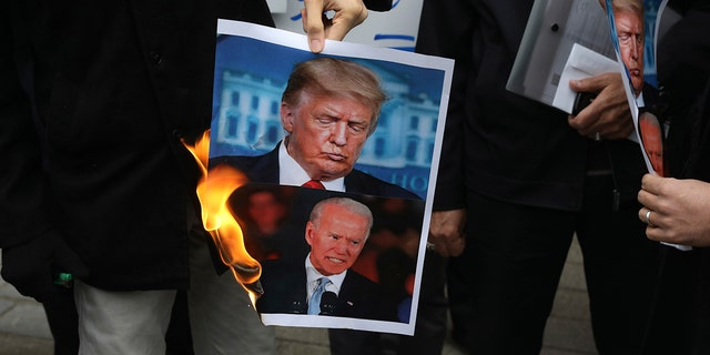A group of protesters burn pictures of the U.S. 도널드 트럼프 대통령, 상단, and the President-elect Joe Biden in a gathering in front of Iranian Foreign Ministry on Saturday, 11 월. 28, 2020, a day after the killing of Mohsen Fakhrizadeh an Iranian scientist linked to the country's nuclear program by unknown assailants near Tehran. (AP Photo/Vahid Salemi)