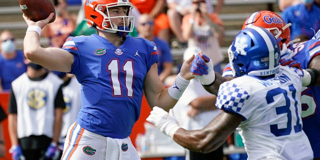 Florida quarterback Kyle Trask (11) throws a pass as Kentucky linebacker Jamar Watson (31) rushes during the first half of an NCAA college football game, Saturday, Nov. 28, 2020, in Gainesville, Fla. (AP Photo/John Raoux)