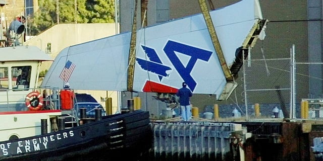A large section of the tailpiece of American Airlines Flight 587 is lifted off a boat by a crane after the Airbus A300 crashed in the Rockaway Beach section of the Queens borough of New York Monday, Nov. 12, 2001. The tailpiece was recovered from Jamaica Bay and towed to shore. (AP Photo/Daniel P. Derella)
