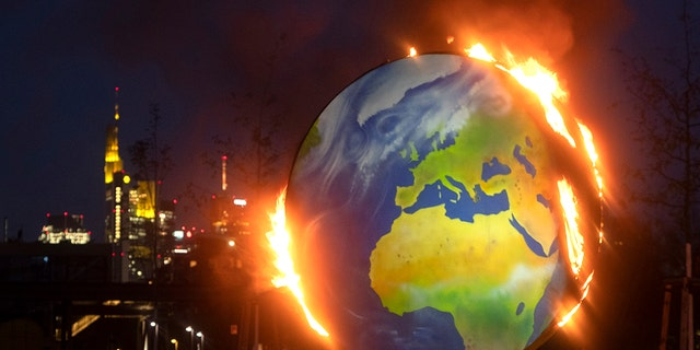 "A makeshift globe burns in front of the European Central Bank in Frankfurt, Germany, Wednesday, Oct. 21, 2020. Activists of the so-called ""KoalaKollektiv,"" an organization asking for climate justice, protested with the burning of the globe against the ECB's climate policy. (AP Photo/Michael Probst)"