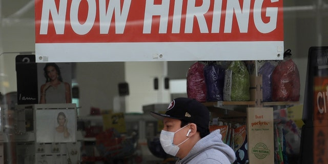 Man wearing a mask while walking under a Now Hiring sign at a CVS Pharmacy during the coronavirus outbreak in San Francisco. (AP Photo/Jeff Chiu, File)