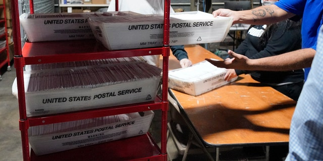 Allegheny County mail services workers, process some of the mail-in and absentee ballots received at the Allegheny County Election Division's Elections warehouse in Pittsburgh, Thursday, Oct. 29, 2020. (AP Photo/Gene J. Puskar)