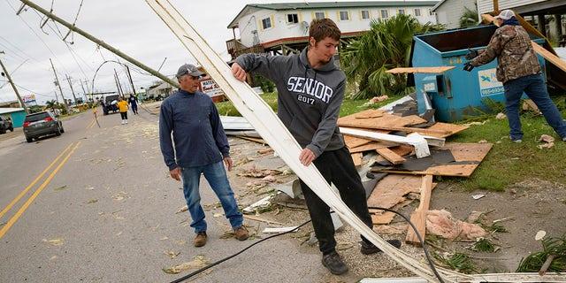 Mark Andollina, izquierda, and his son, Nicholas Andollina, center, remove part of a roof damaged by Hurricane Zeta at the Cajun Tide Beach Resort in Grand Isle, La., Friday, Oct. 30, 2020. (AP Photo/Matthew Hinton)