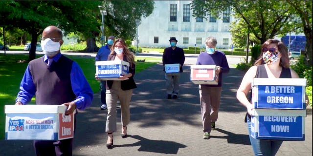 This photo from video provided by the Yes on Measure 110 Campaign shows volunteers delivering boxes containing signed petitions in favor of the measure to the Oregon Secretary of State's office in Salem on June 26, 2020.