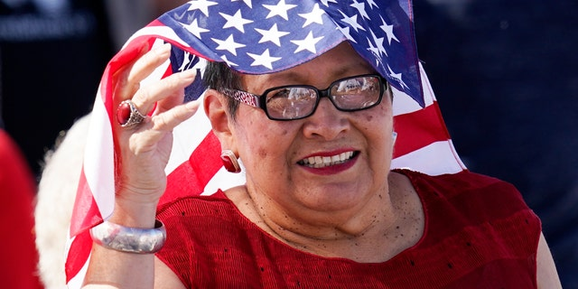 A supporter of Vice President Mike Pence smiles as she waits for Pence to speak at a campaign rally at Tucson International Airport Friday, Oct. 30, 2020, in Tucson, Ariz. (AP Photo/Ross D. Franklin)