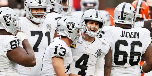 Las Vegas Raiders quarterback Derek Carr (4) and wide receiver Hunter Renfrow (13) celebrate after Renfrow scored a 4-yard touchdown during the second half of an NFL football game against the Cleveland Browns, Sunday, Nov. 1, 2020, in Cleveland. (AP Photo/Ron Schwane)
