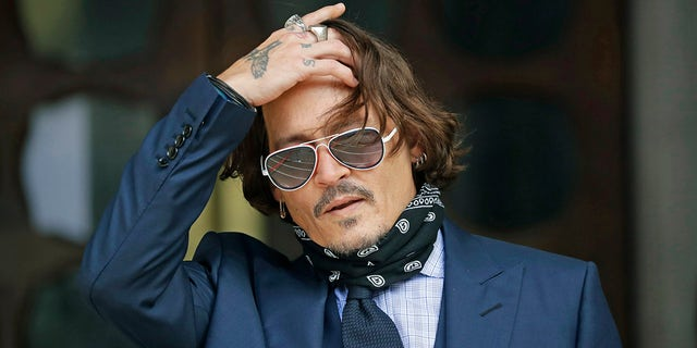 In this Tuesday, July 14, 2020 file photo, American actor Johnny Depp gestures to the media as he arrives at the High Court in London.