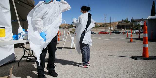 Jacob Newberry puts on new PPE at the COVID-19 state drive-thru testing location at UTEP in El Paso, Texas on Oct. 26, 2020. (Briana Sanchez/The El Paso Times via AP, File)