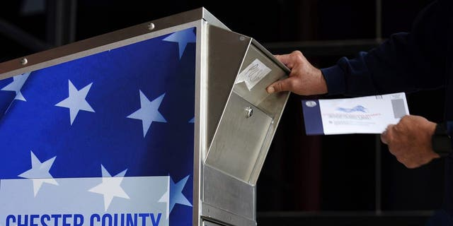 In this Oct. 23, 2020, file photo, a man drops off his ballot for the 2020 General Election in the United States outside the Chester County Government Services Center in West Chester, Penn. (AP Photo/Matt Slocum, File)