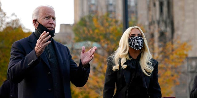 Democratic presidential candidate former Vice President Joe Biden stands with Lady Gaga at Schenley Plaza, Monday, Nov. 2, 2020, in Pittsburgh, Pa. (AP Photo/Andrew Harnik)
