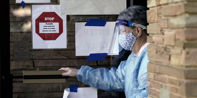 Poll-worker Dina Grinstead assists voters at the Graham Civic Center polling location in Graham, N.C., Tuesday, Nov. 3, 2020. (AP Photo/Gerry Broome)