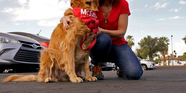 NOI. Suo. Martha McSally, R-Ariz., hugs her dog Boomer prior to greeting voters at a polling station, martedì, Nov. 3, 2020, in Mesa, Ariz. (AP Photo/Matt York)