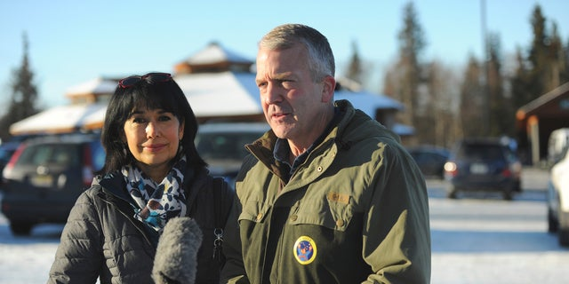 Incumbent Republican Sen. Dan Sullivan, left, with his wife Julie, speaks to the media after casting his ballot at the Alaska Zoo Tuesday, Nov. 3, 2020, in Anchorage, Alaska. (AP Photo/Michael Dinneen)