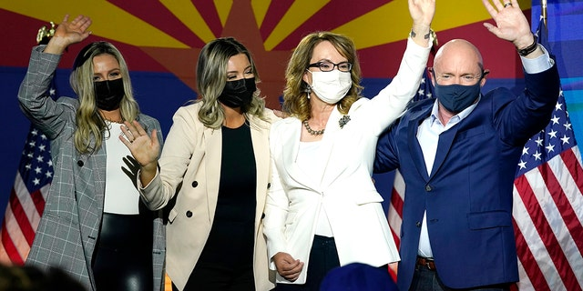 Sen. Mark Kelly, D-Ariz., waves to supporters along with his wife Gabrielle Giffords, second from right, and daughters, Claire Kelly, left, and Claudia Kelly, second from left, during an election night event Tuesday, Nov. 3, 2020 in Tucson, Ariz. Kelly is up for reelection in 2022. (AP Photo/Ross D. Franklin)