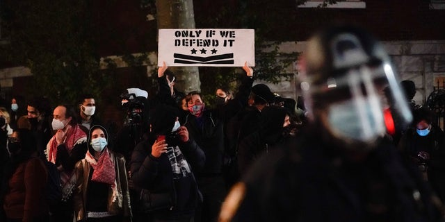 Demonstrators shout at New York Police officers as they protest in Washington Square Park, Wednesday, Nov. 4, 2020, in New York. (AP Photo/Seth Wenig)
