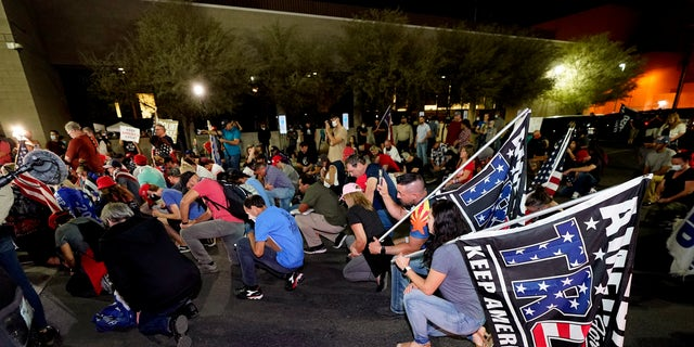 Trump supporters kneel as they rally Wednesday night outside the Maricopa County Recorders Office in Phoenix. (Associated Press)