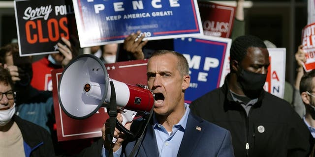 President Donald Trump's campaign adviser Corey Lewandowski, center, speaks about a court order obtained to grant more access to vote counting operations at the Pennsylvania Convention Center, Thursday, Nov. 5, 2020, in Philadelphia, following the election. (AP Photo/Matt Slocum)