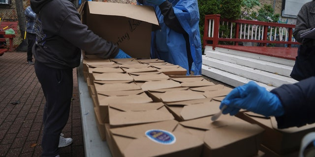Volunteers unload boxed meals prepared at La Morada, 수요일에, 10 월. 28, 2020, 뉴욕에서. (AP Photo/Bebeto Matthews)