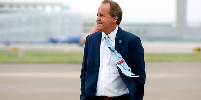 In this June 28, 2020, file photo, Texas Attorney General Ken Paxton waits on the flight line for the arrival of Vice President Mike Pence at Love Field in Dallas. Paxton had an extramarital affair with a woman whom he later recommended for a job with the wealthy donor now at the center of criminal allegations against him, according to two people who said Paxton told them about the relationship. (AP Photo/Tony Gutierrez, File)