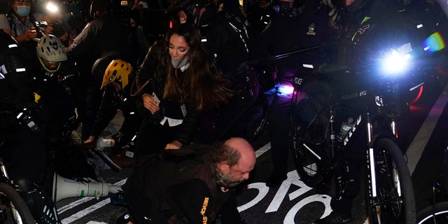 New York Police bike patrol officers corral demonstrators and members of the media during a march through the West Village, on Thursday. (Associated Press)