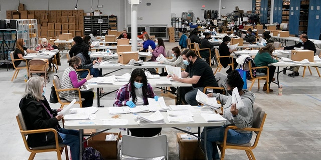 Officials work on ballots at the Gwinnett County Voter Registration and Elections Headquarters, Friday, Nov. 6, 2020, in Lawrenceville, near Atlanta. (AP Photo/John Bazemore)