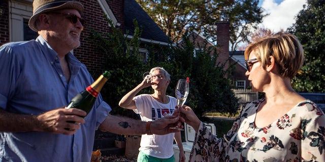 Damon Akins, 从左起, Colleen Trimble and Kathryn Shields drink champagne at a celebration for President-elect Joe Biden in Greensboro, N.C., 周六, 十一月. 7, 2020.<br> (Khadejeh Nikouyeh/News &安培; Record via AP)