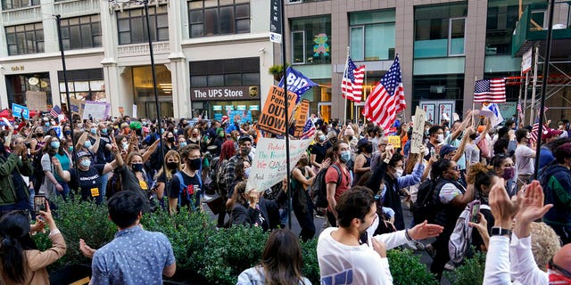 Outdoor diners cheer as as demonstrators march through the streets after former vice president and Democratic presidential candidate Joe Biden was announced as the winner over Pres. Donald Trump Nov. 7. (AP Photo/Seth Wenig)