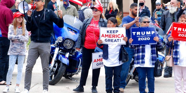 "Hundreds of supporters of President Donald Trump staged a defiant rally outside the New Mexico state Capitol building in Santa Fe, N.M., on Nov. 7. They waved flags, chanted ""four more years,"" and cheered and jeered at passing cars. A dozen supporters of Democrat Joe Biden gathered blocks away at the city's central plaza amid a heavy police presence. Democrat Joe Biden won the vote for New Mexico in the Nov. 3 election. (AP Photo/Morgan Lee)"