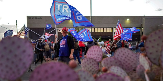 Pro Trump supporters rally outside the Maricopa County Recorder's Office, Saterdag, Nov.. 7, 2020, in Phoenix. President-elect Joe Biden defeated President Donald Trump on Saturday to become the 46th president of the United States. (AP Photo/Matt York)
