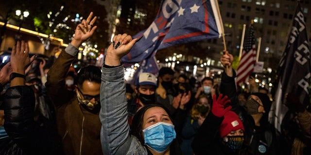 Brittney Hernandez celebrates Joe Biden's win in the presidential election, Saturday, Nov. 7, 2020, in Portland, Ore. (AP Photo/Paula Bronstein)