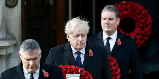 Britian's Prime Minister Boris Johnson carries a wreath, during the Remembrance Sunday service at the Cenotaph, in Whitehall, London, Sunday, Nov. 8, 2020.