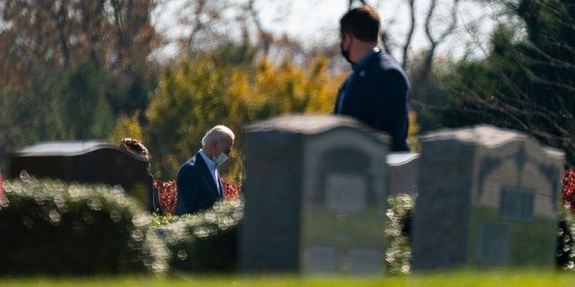 조 바이든 당선자, 왼쪽, visits the cemetery where his son Beau, his wife Neilia, and daughter Naomi are buried at St. Joseph on the Brandywine Catholic Church, 일요일, 11 월. 8, 2020, 윌 밍턴, 의. At right is a member of the secret service keeping watch. (AP Photo/Carolyn Kaster)