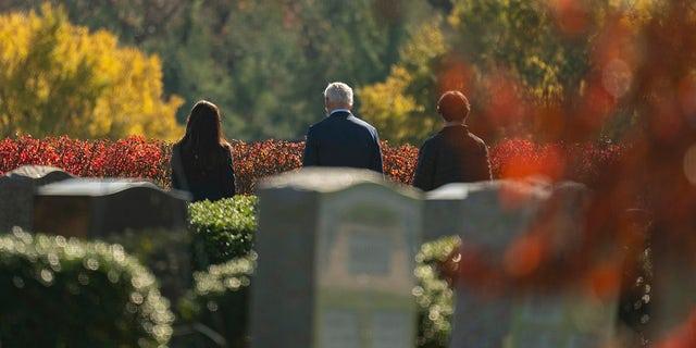 조 바이든 당선자, 센터, visits the cemetery where his son Beau, his wife Neilia, and daughter Naomi are buried at St. Joseph on the Brandywine Catholic Church, 일요일, 11 월. 8, 2020, 윌 밍턴, 의. (AP Photo/Carolyn Kaster)