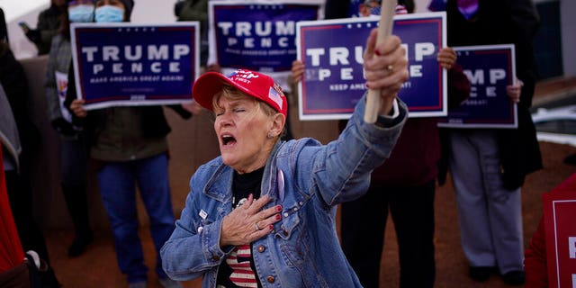 A supporter of President Donald Trump grabbed her heart during a protest against the election outside the Clark County Elections Department, Sunday, November 8, 2020, in North Las Vegas.
