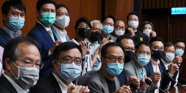 Hong Kong's pro-democracy legislators pose a picture before a press conference at the Legislative Council in Hong Kong, Monday, Nov. 9, 2020. (AP Photo/Vincent Yu)
