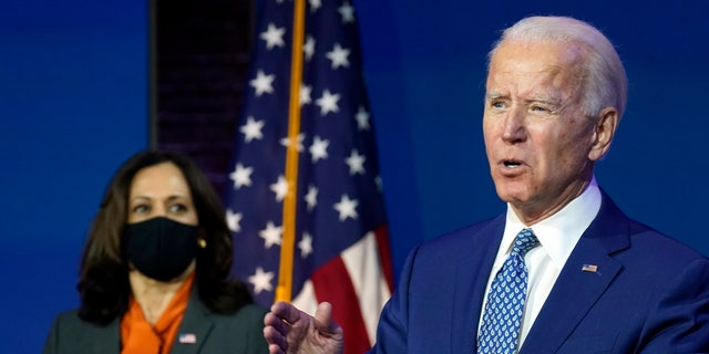 President-elect Joe Biden speaks Monday, Nov. 9, 2020, at The Queen Theater in Wilmington, Del., as Vice President-elect Kamala Harris listens. Both will stump for the Georgia Democratic Senate candidates in the final week of the campaign. (AP Photo/Carolyn Kaster)