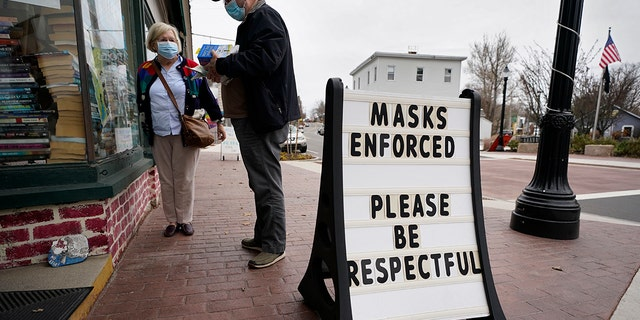 Shoppers comply with the mask regulations to help prevent the spread of the coronavirus at Bridgton Books, Friday, Nov. 13, 2020, in Bridgton, Maine.  (AP Photo/Robert F. Bukaty)